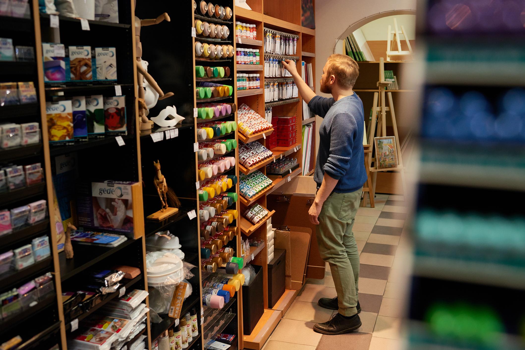 Guy choosing paint in modern store